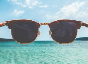 óculos de sol com paisagem do mar e ceu