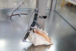 óculos com armação transparente da marca da visão plus na montra com decoração de conha da praia
