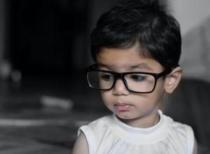criança pequena com óculos de armação preta